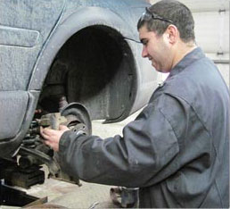 male student fixing a car