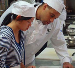 female student working with chef in kitchen