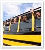 children waving from bus window