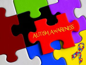 puzzle pieces. one has the words autism awareness on it