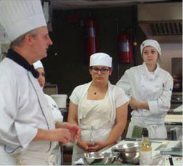 2 female students listening to chef in kitchen