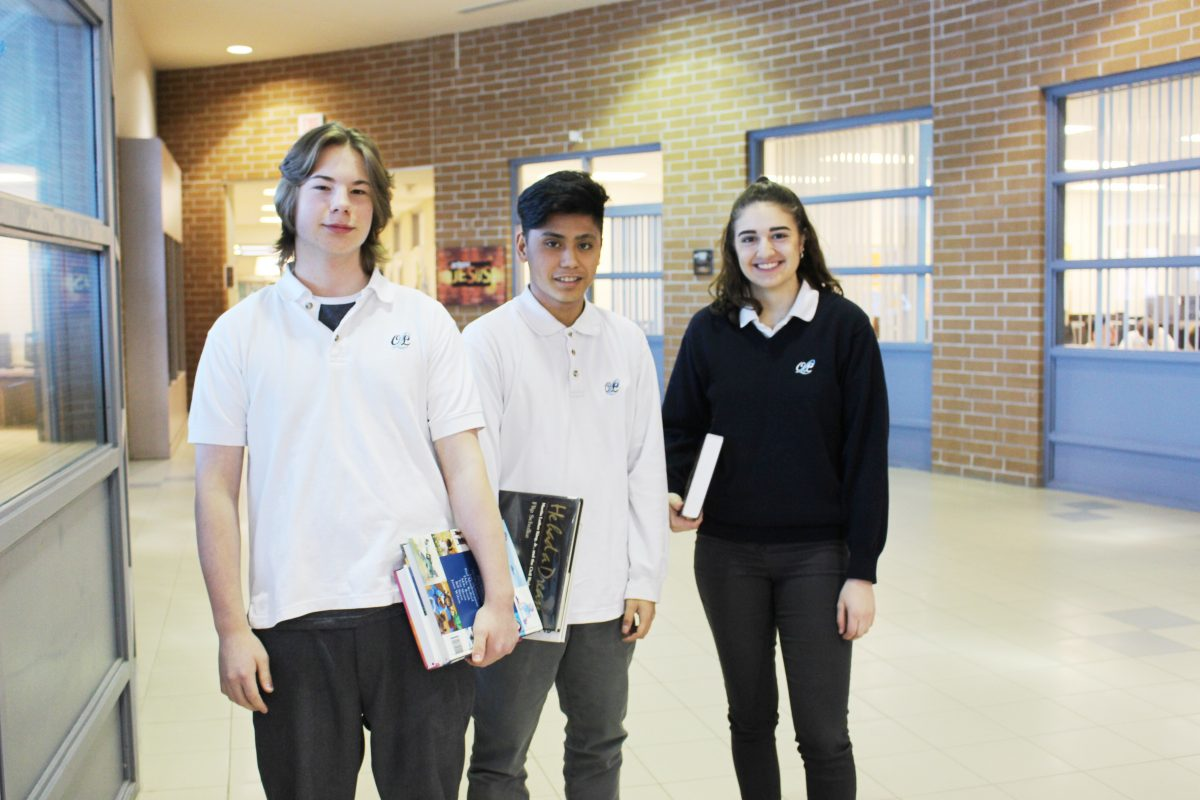 3 students standing in the school hallway holding books