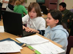 two students sti in front of a laptop in a classroom setting