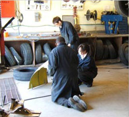 3 students working in auto shop